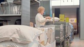 Cliente femenino mayor que elige la nueva almohada ortopédica en la tienda del mobiliario almacen de metraje de vídeo