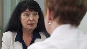 Cliente femenino mayor que habla con el doctor de sexo femenino en hospital metrajes
