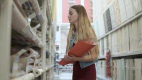 Cliente femenino que elige los nuevos papeles pintados metrajes