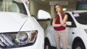 Cliente femenino que examina el nuevo coche en el dealershop almacen de metraje de vídeo