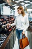 Cliente femenino que mira los cosméticos en tienda del maquillaje fotos de archivo libres de regalías
