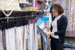 Cliente femenino que mira telas interiores Imagen de archivo libre de regalías