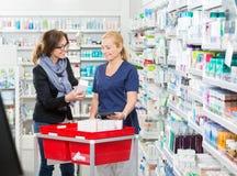 Cliente femenino que muestra el producto al químico Imágenes de archivo libres de regalías