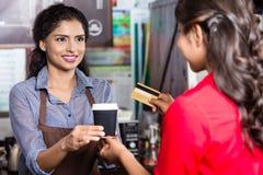 Cliente femenino que paga el café con la tarjeta de crédito foto de archivo libre de regalías