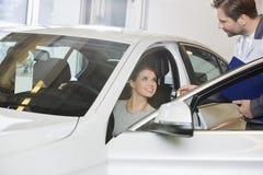 Cliente femenino que recibe llave del coche de mecánico en el taller de reparaciones del automóvil Imágenes de archivo libres de regalías