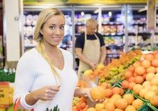 Cliente femenino que se considera anaranjado en supermercado Foto de archivo libre de regalías
