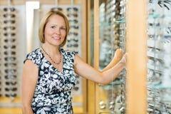 Cliente femenino que selecciona los vidrios en óptico imagenes de archivo