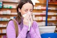 Cliente femenino que sufre de frío en farmacia Fotografía de archivo