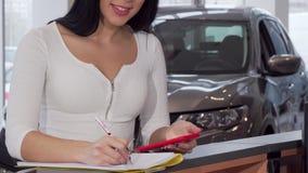 Cliente femenino que usa el teléfono elegante mientras que firma los documentos para el nuevo automóvil metrajes