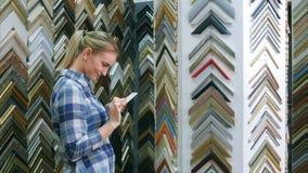 Cliente femenino sonriente que busca el marco, soporte cercano permanente del marco en taller Foto de archivo