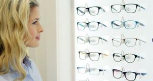 Cliente femenino sonriente que selecciona gafas metrajes