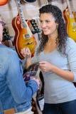 Cliente femminile che cerca nuova chitarra in deposito e nel sorridere immagini stock libere da diritti