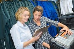 Cliente femminile che sceglie l'uniforme di destra Fotografie Stock Libere da Diritti