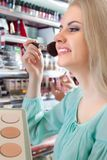 Cliente femminile che sceglie la polvere della pelle immagine stock libera da diritti