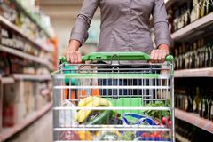 Cliente femminile con il carrello al supermercato Immagine Stock