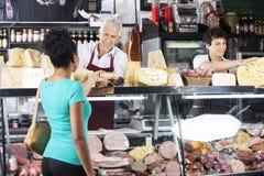 Cliente femminile di Giving Cheese To del rappresentante al contatore fotografie stock libere da diritti