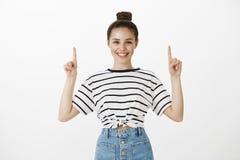 Cliente femminile europeo soddisfatto piacevole con l'acconciatura del panino in maglietta a strisce, indicante verso l'alto e so Fotografia Stock Libera da Diritti