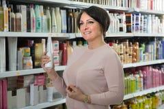Cliente femminile felice che sceglie condizionatore per capelli in st di bellezza immagine stock