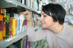 Cliente femminile felice che sceglie condizionatore per capelli in st di bellezza immagine stock libera da diritti