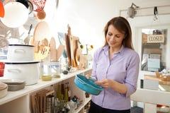 Cliente femminile maturo che esamina piatto in cuoco Shop Fotografia Stock Libera da Diritti