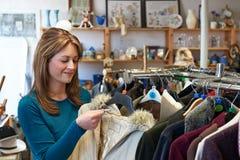 Cliente femminile nel deposito di risparmio che esamina i vestiti Fotografia Stock