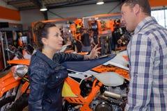Cliente femminile sorridente che compra nuova motocicletta in officina fotografia stock