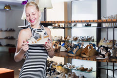 Cliente femminile sorridente dei giovani che prova sulle paia dei sandali Fotografia Stock