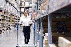 Cliente grazioso asiatico che cerca i prodotti nel magazzino del deposito La ragazza che spinge il carretto e trovare le merci pe fotografia stock libera da diritti
