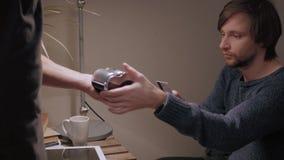 Cliente hermoso del hombre que paga por la tarjeta de crédito sin contacto en café moderno almacen de metraje de vídeo
