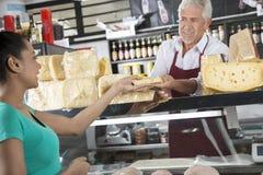 Cliente heureuse de femelle de Selling Cheese To de vendeur Photographie stock