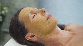 Cliente incantante che si trova nel salone della stazione termale con la pelatura della maschera sul fronte stock footage