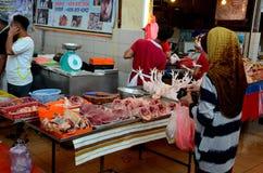 Cliente malayo de la mujer en los mariscos halal del pollo de la carne fresca del carnicero en el mercado mojado Kuching Sarawak  imágenes de archivo libres de regalías