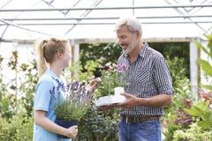 Cliente maschio che chiede al personale il consiglio della pianta al Garden Center fotografia stock