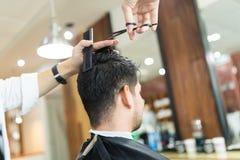 Cliente maschio che ottiene taglio di capelli dallo stilista in salone fotografia stock