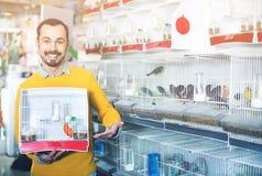 Cliente maschio che si vanta il suo acquisto dell'uccello color giallo canarino Immagine Stock