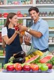 Cliente maschio con la venditora Comparing Bellpepper Immagini Stock