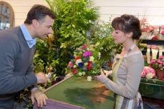 Cliente maschio d'aiuto del venditore per scegliere i fiori fotografia stock