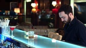 Cliente masculino con el dinero del efectivo que paga cóctel en barra metrajes
