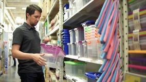 Cliente masculino en la tienda Él que toma el envase de plástico del estante almacen de metraje de vídeo