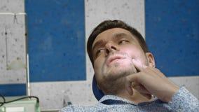 Cliente masculino en punto dolorido de la demostración dental de la oficina a su dentista Fotos de archivo
