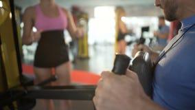 Cliente masculino encorajador do treinador fêmea a exercitar acima e dar forma no gym video estoque