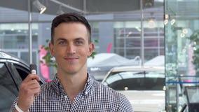 Cliente masculino feliz que muestra los pulgares encima de llevar a cabo llaves del coche en la representación metrajes