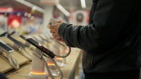 Cliente masculino joven que elige un nuevo teléfono móvil en una tienda Él está intentando cómo trabaja almacen de metraje de vídeo