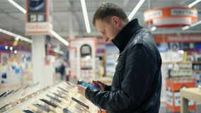 Cliente masculino joven que elige un nuevo teléfono móvil en una tienda, comprobando cómo trabaja almacen de metraje de vídeo