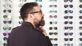Cliente masculino maduro que elige los vidrios en la tienda de las gafas almacen de metraje de vídeo