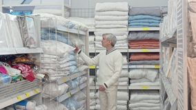 Cliente masculino mayor que elige la tienda de las mercancías del lecho en casa metrajes