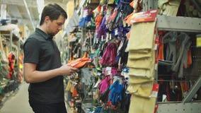 Cliente masculino na loja de ferragens que escolhe luvas do jardim vídeos de arquivo