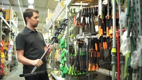 Cliente masculino na loja do jardim que escolhe o eixo helicoidal manual para a broca do furo vídeos de arquivo