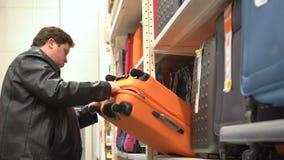 Cliente masculino que elige la maleta anaranjada para viajar Escena en el supermercado almacen de metraje de vídeo