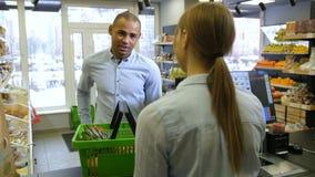 Cliente masculino que paga con la tarjeta de crédito al cajero almacen de video